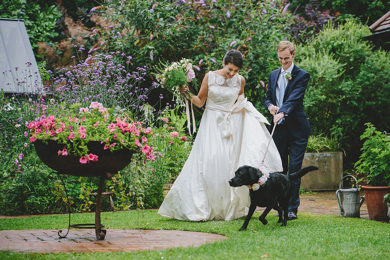 bride and groom with dog in floral collar